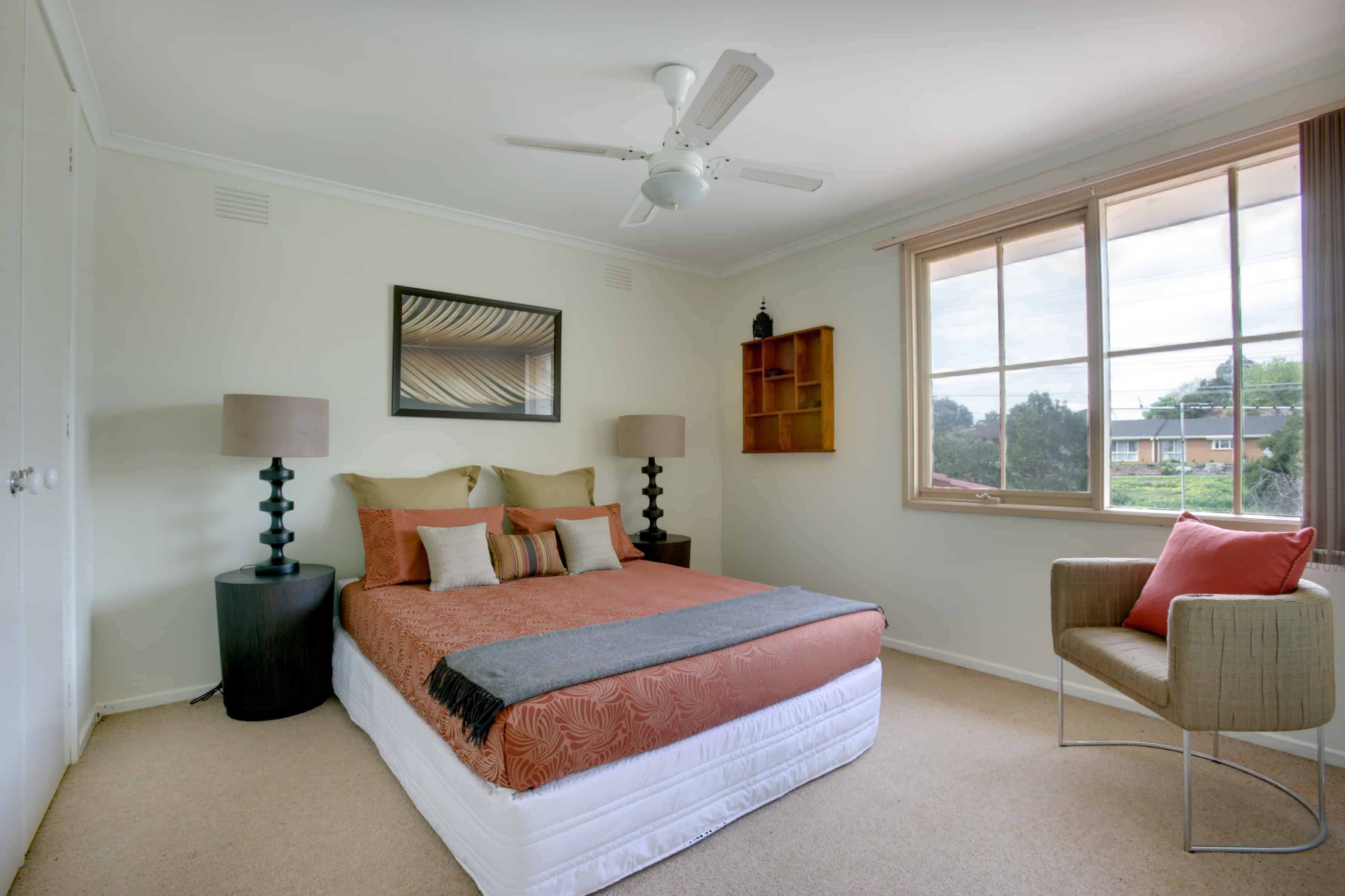 A modern bedroom with minimal furniture . The coloring is neutral that makes the beautiful black lamp shades pop even more. The large window allows lots of natural light coming through.