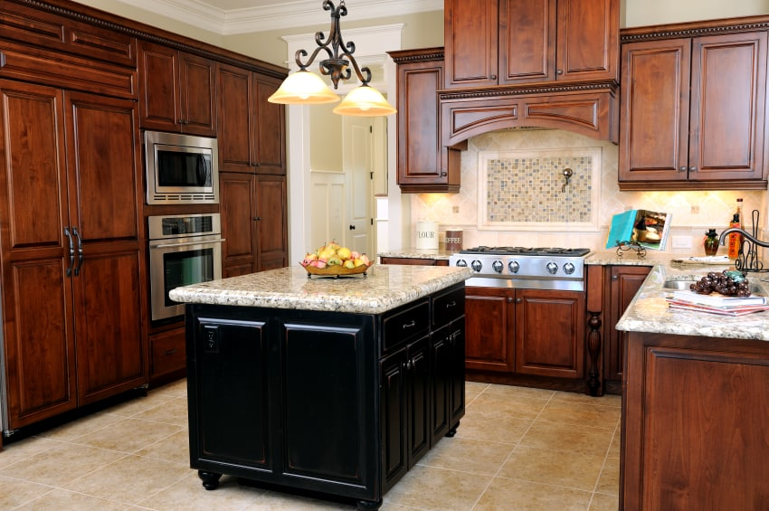 A kitchen with mismatched wood colors used in cabinets and island. The cabinets are made of cherry wood against a light colored backsplash. On the other hand, the black wooden island pop over beige tile flooring .