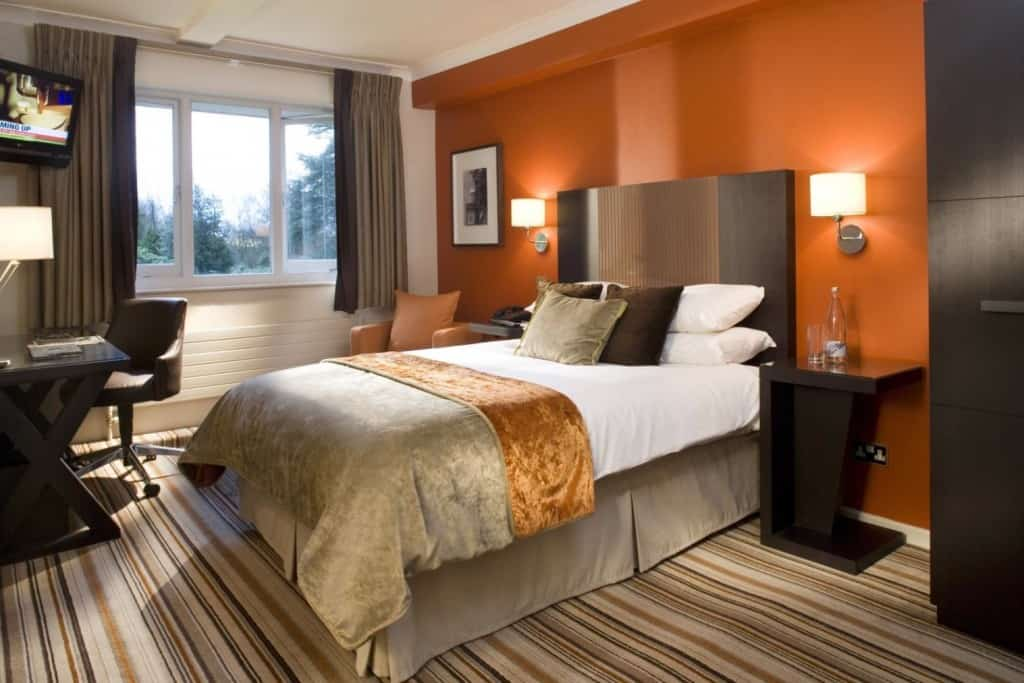 A classy bedroom that uses colorful striped floor carpet, dark furniture and a large cabinet. The head side wall is red orange while the other walls and roof are white.