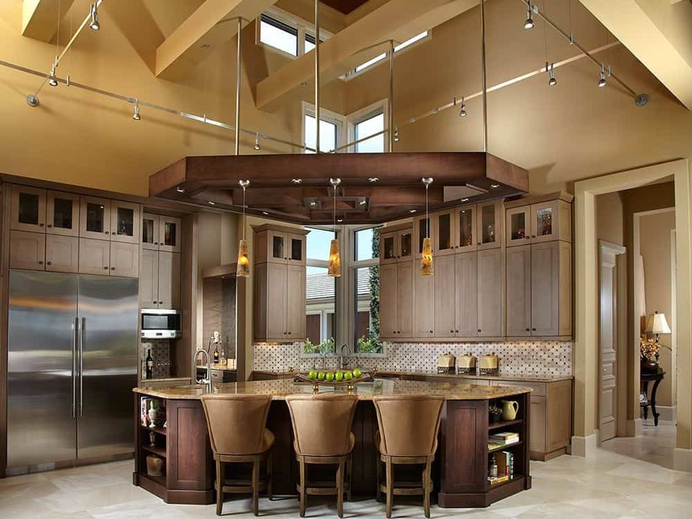 The dark wooden structure hanging above easily grabs attention of this corner kitchen . The island is triangular topped by brownish marble. The walls contain upper and lower wooden cabinets .