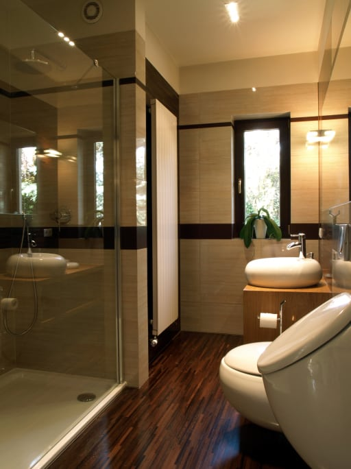bathroom with natural wooden vanity and dark hard wooden flooring